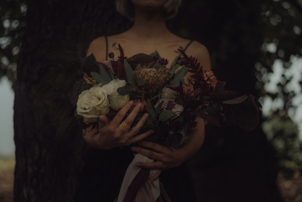 Dark rock'n'roll bride holding the bridal bouquet, italy